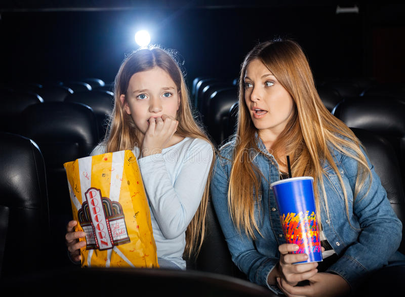 Woman Looking At Scared Daughter Watching Movie stock images