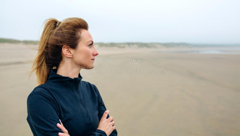 Woman looking at sea. On the beach in autumn stock photos