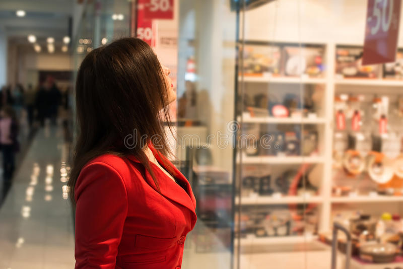 Woman looking at the shop window. Portrait of an attractive young woman looking at the shop window stock images