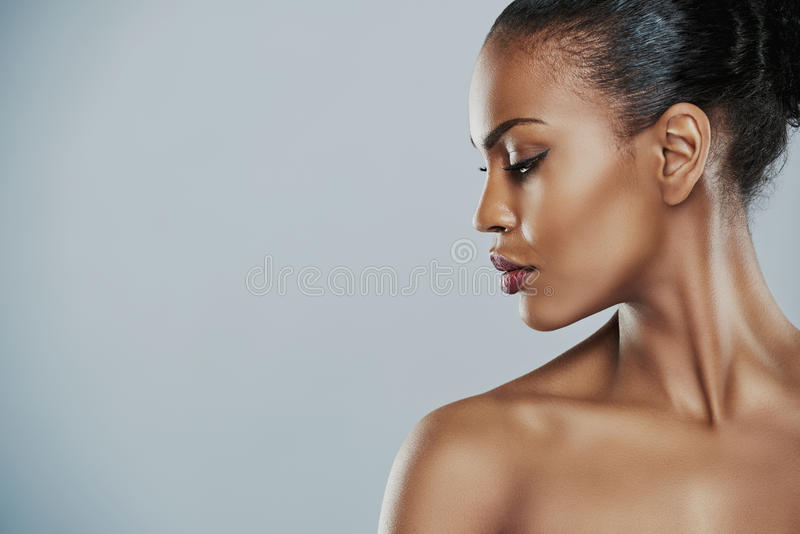 Woman looking sideways over gray background. Profile view of beautiful grinning African bare shouldered female with short hair looking sideways over gray royalty free stock photography