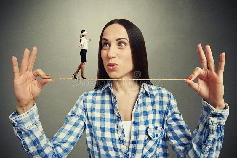 Woman looking at small walking woman stock images