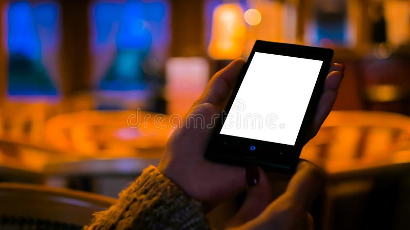 Woman looking at smart phone phone with white empty display in cafe royalty free stock image