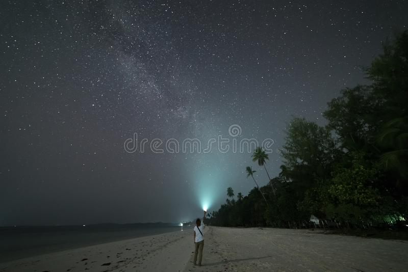 Woman looking at stars and milky way on sand beach, torch light on night sky, rear view, real people. Indonesia, Kei islands, royalty free stock photos