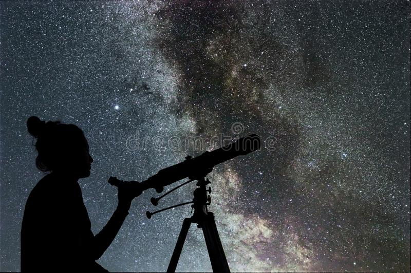 Woman looking at the stars with telescope beside her royalty free stock photo