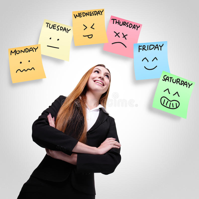 Woman looking stickers with week of face expression. Young woman looking up with color stickers displaying day of week and face expression on each separate color stock image