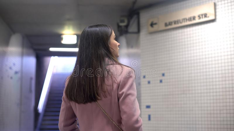 Woman looking at street pointer in underground, tourist lost in big unknown city stock images