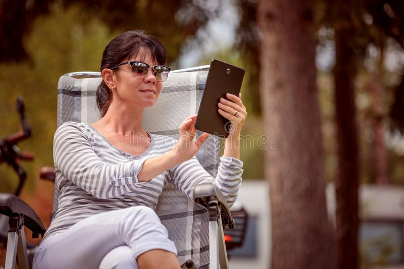 Family vacation travel, holiday trip in motorhome RV. Woman looking at the tablet near the camping . Caravan car Vacation. Family vacation travel, holiday trip stock image