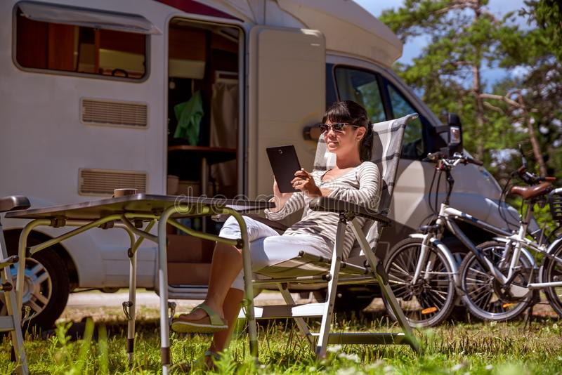 Family vacation travel, holiday trip in motorhome RV. Woman looking at the tablet near the camping . Caravan car Vacation. Family vacation travel, holiday trip royalty free stock photography
