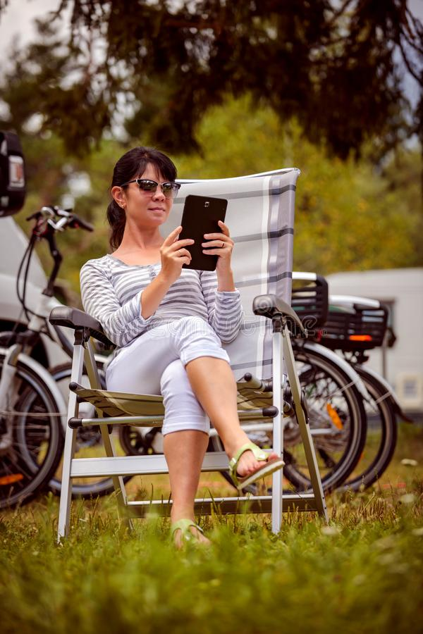Family vacation travel, holiday trip in motorhome RV. Woman looking at the tablet near the camping . Caravan car Vacation. Family vacation travel, holiday trip royalty free stock photos