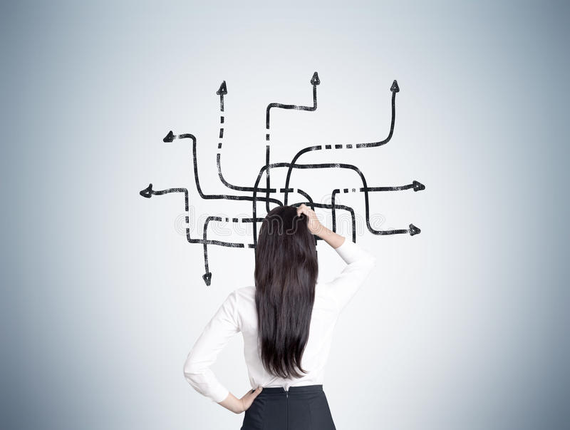Woman looking at tangled arrows on gray wall stock photo