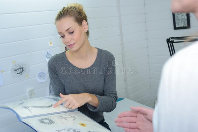 Woman looking at tattoo designs. Tattoo royalty free stock photography