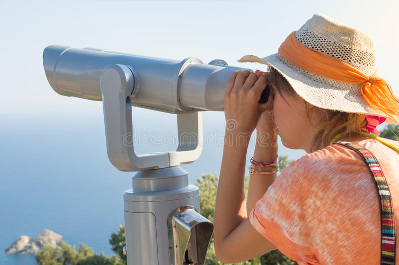 Woman looking thru binoculars at the horizon. royalty free stock photography