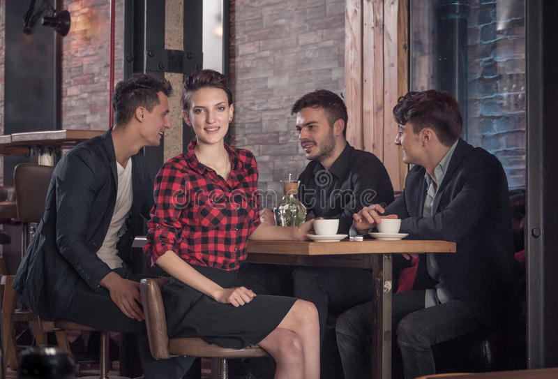 Woman looking to the camera, small group of people, coffee shop stock image