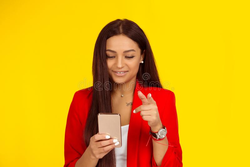 Woman looking to a message in her phone smile and pointing at you camera with finger stock photos
