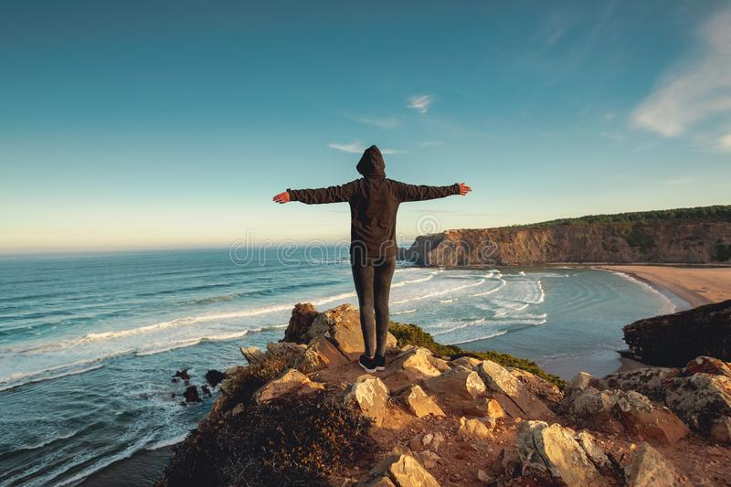 Freedom. Woman looking to the ocean with arms wide open stock images