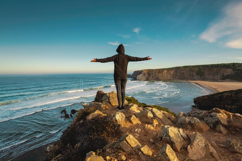Freedom. Woman looking to the ocean with arms wide open royalty free stock photo