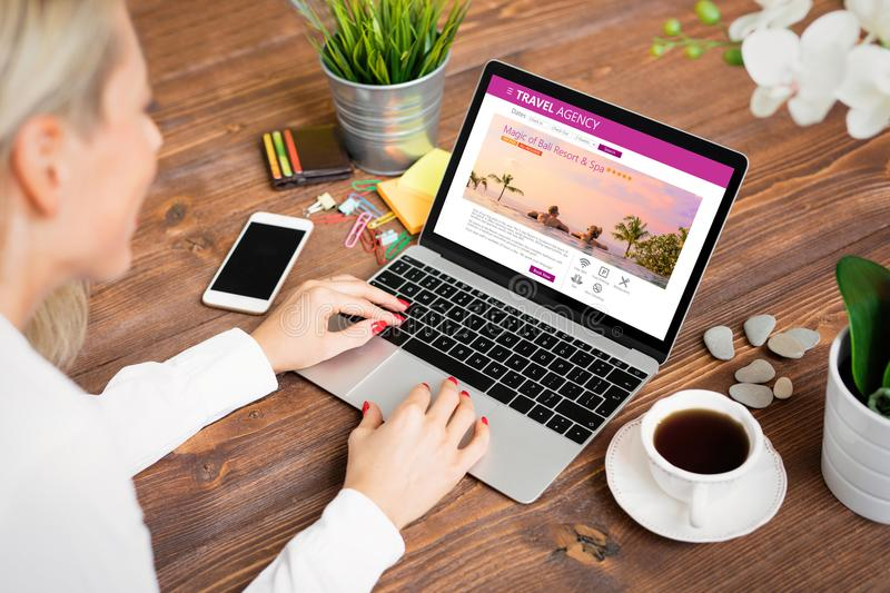 Woman looking for travel accommodations. Woman searching travel in travel agency stock photo