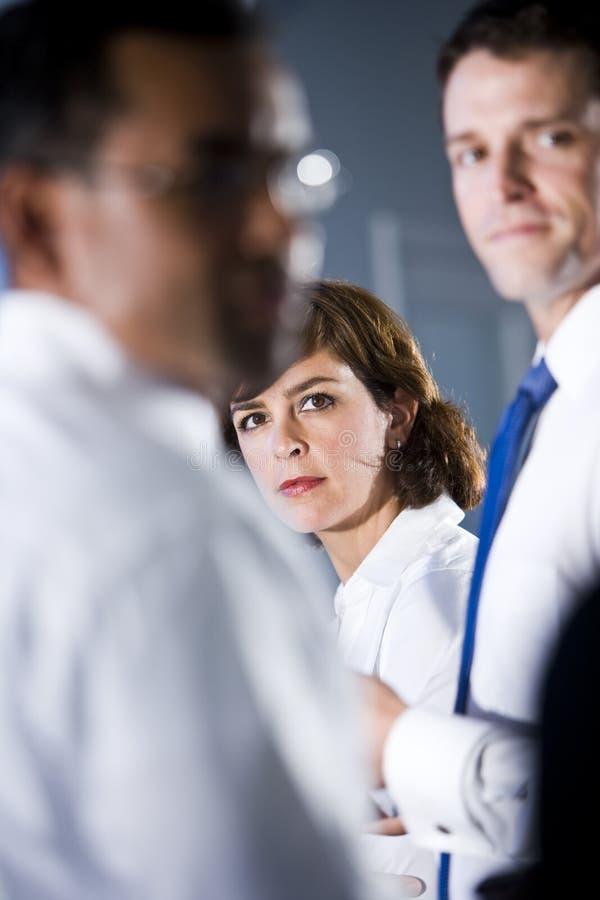 Woman looking between two businessmen stock image