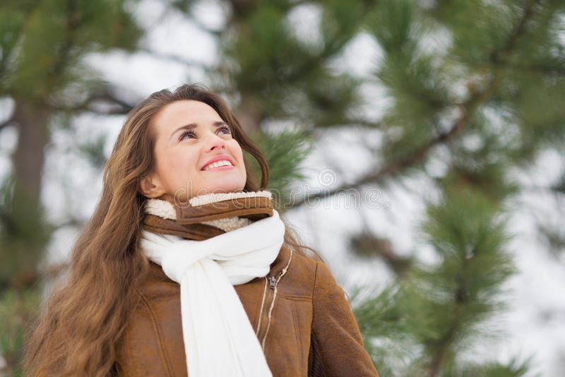 Woman looking up on copy space in winter outdoors. Happy young woman looking up on copy space in winter outdoors stock photography