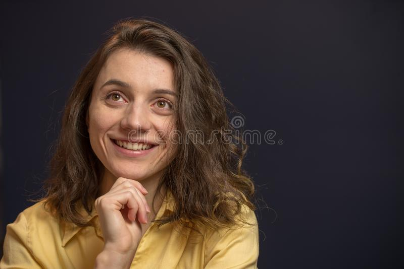 Woman looking up with happy expresison. Woman looking happy with hand on chin in yellow shirt with dark blue walls royalty free stock photography