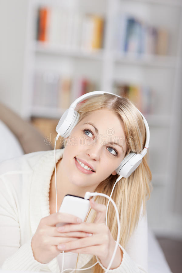 Woman Looking Up While Listening Music On Headphones stock photography