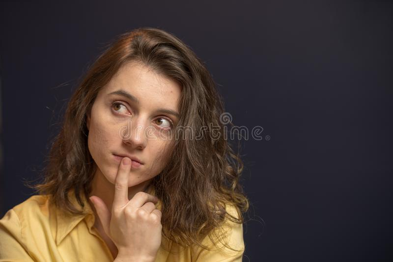 Woman looking up with puzzled expresison. Woman looking puzzled with finger over mouth in yellow shirt with dark blue walls stock image