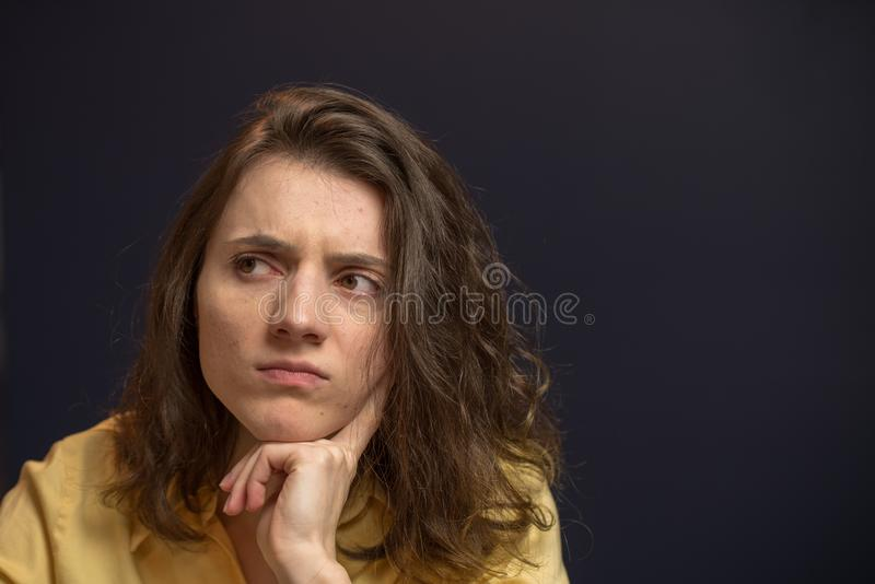 Woman looking up with puzzled expresison. Woman looking puzzled in yellow shirt with dark blue walls royalty free stock photos