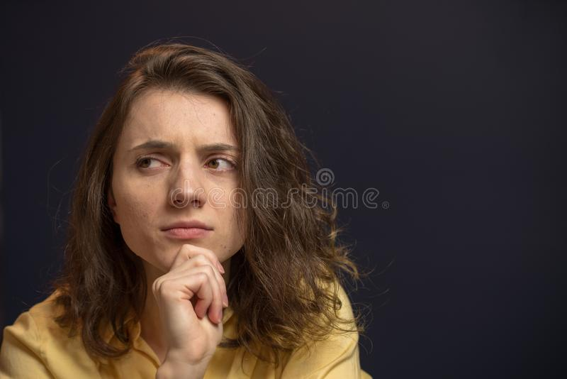 Woman looking up with puzzled expresison. Woman looking puzzled in yellow shirt with dark blue walls royalty free stock image