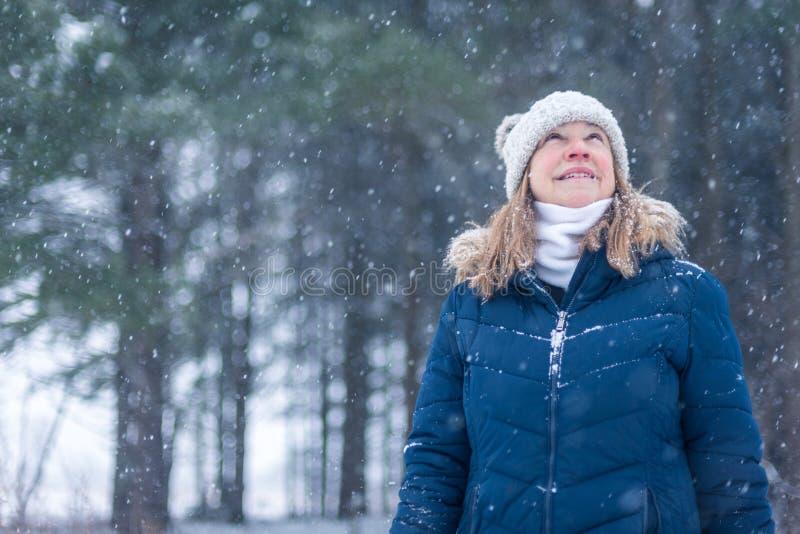 Woman looking up at snow falliing stock photo