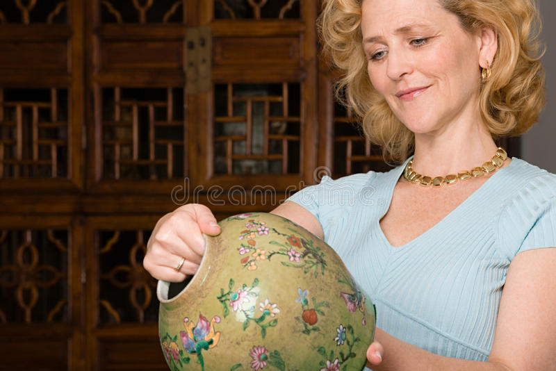 Woman looking at a vase stock photography