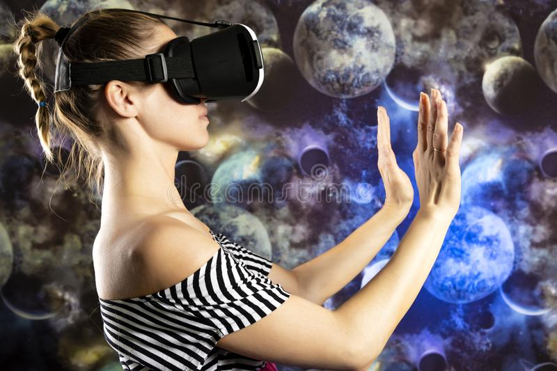 A woman is looking through virtual reality at space. Space background royalty free stock photo