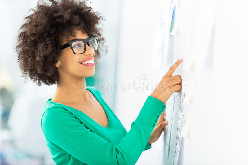 Woman looking at wall with adhesive notes stock photo