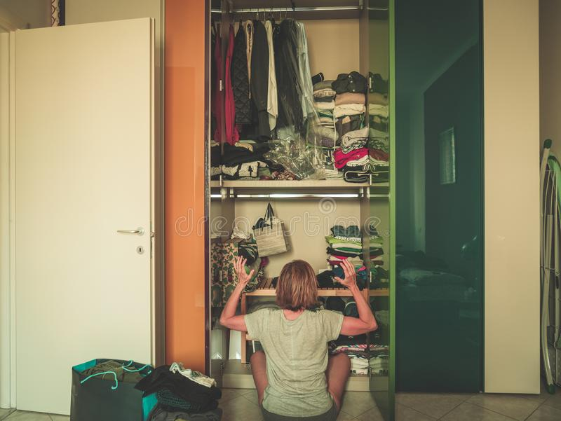 Woman looking at wardrobe, home interior, desperate housewife, cleaning home, rear view sitting, toned vintage style. royalty free stock photos