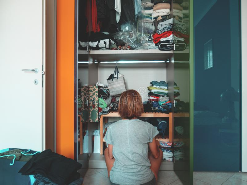 Woman looking at wardrobe, home interior, desperate housewife, cleaning home, rear view sitting, toned vintage style. royalty free stock photography