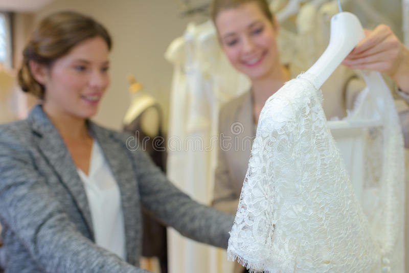 Woman looking at wedding dress in store stock photos