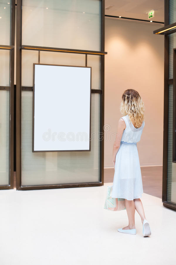 Woman looking at white blank poster. Focus on a woman stock photos