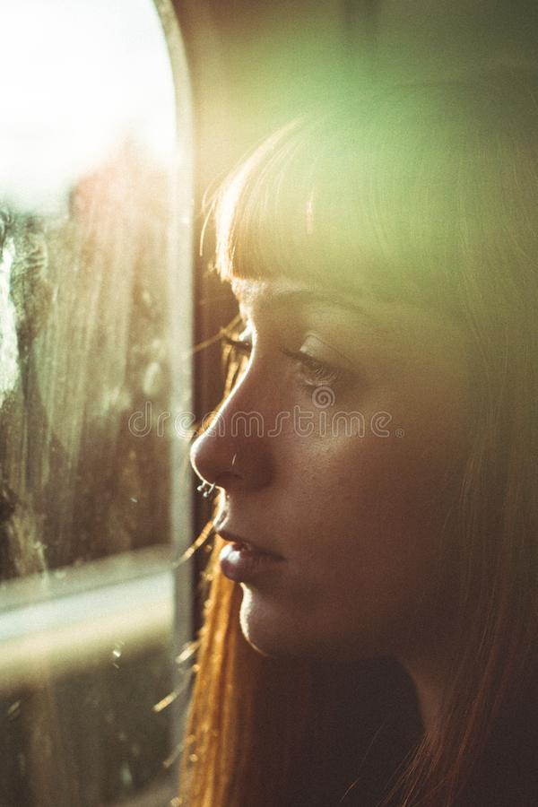 Woman Looking Through a Window royalty free stock image