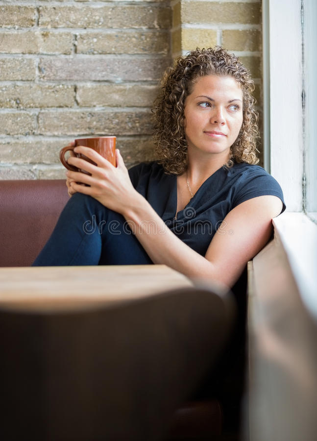 Woman Looking Through Window In Cafeteria. Mid adult woman with coffee mug looking through window in cafeteria royalty free stock image