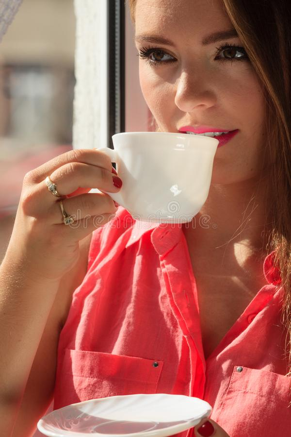 Woman looking through window, relaxing drinking coffee stock photography
