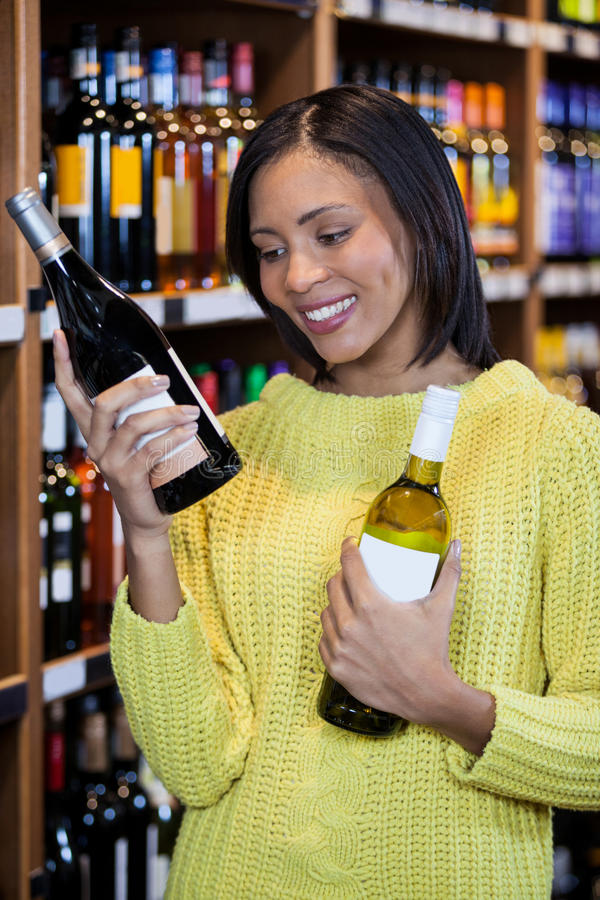 Woman looking at wine bottle in grocery section royalty free stock images