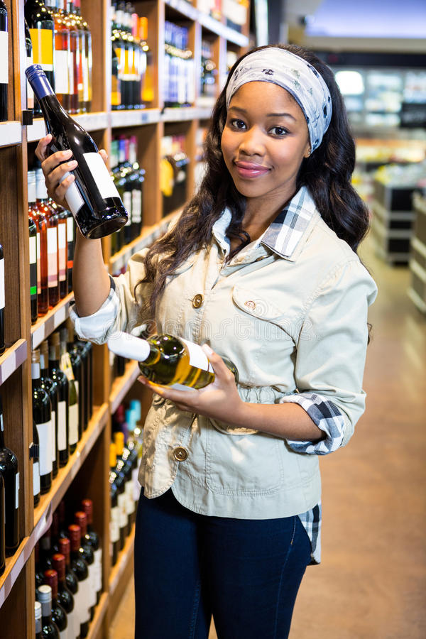 Woman looking at wine bottle in grocery section at supermarket. Portrait of woman looking at wine bottle in grocery section at supermarket royalty free stock photos