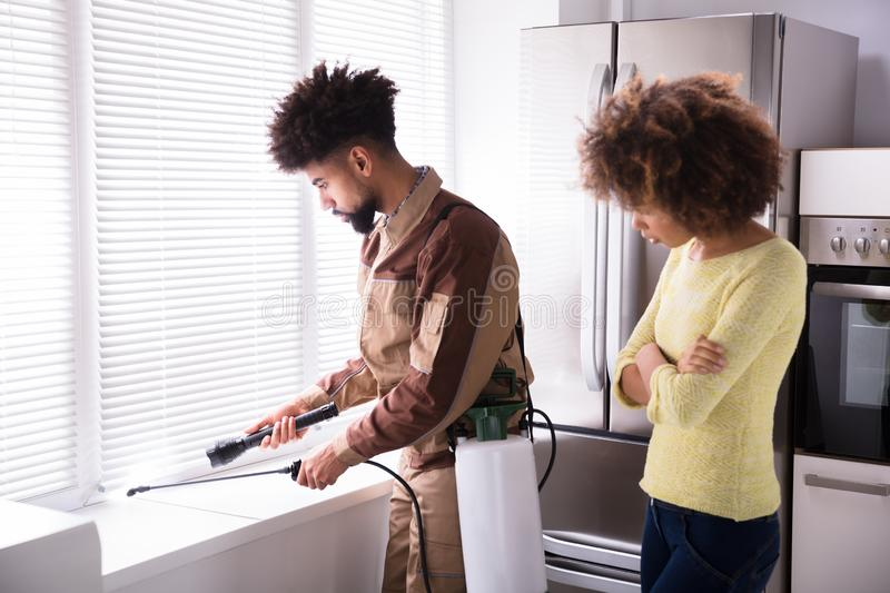 Pest Control Worker Spraying Insecticide On Window Sill. Woman Looking At Young Male Pest Control Worker Spraying Insecticide On Window Sill royalty free stock photo