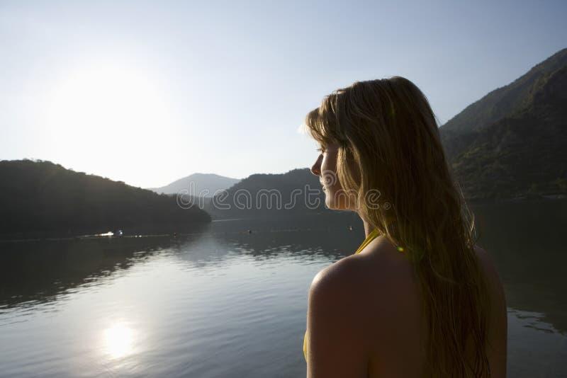 Woman Looks Across Sunrise Over Lake. Blonde woman looking out across morning sunrise over lake royalty free stock photography