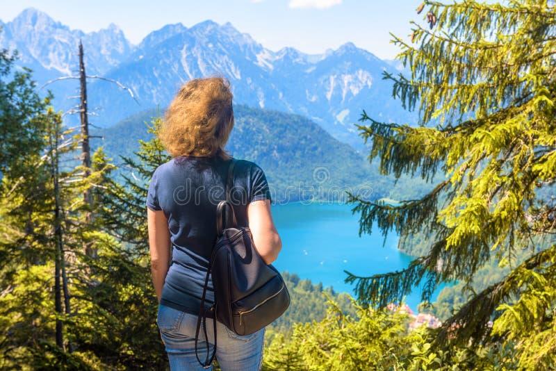 Woman looks at Alpine landscape, Bavaria, Germany. Scenic view to Alpsee lake near Schwangau village royalty free stock photo