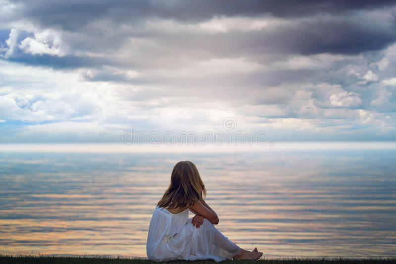 Woman looks at colorful light reflections. Over the lake waters royalty free stock photo