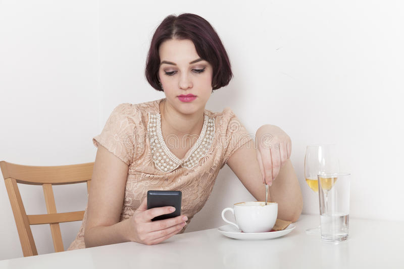 Woman looks disappointed to her mobile phone. Woman receives a message due to canceled date with her in a cafeteria royalty free stock images