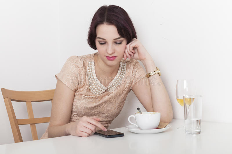 Woman looks disappointed to her mobile phone. Woman receives a message due to canceled date with her in a cafeteria stock photo