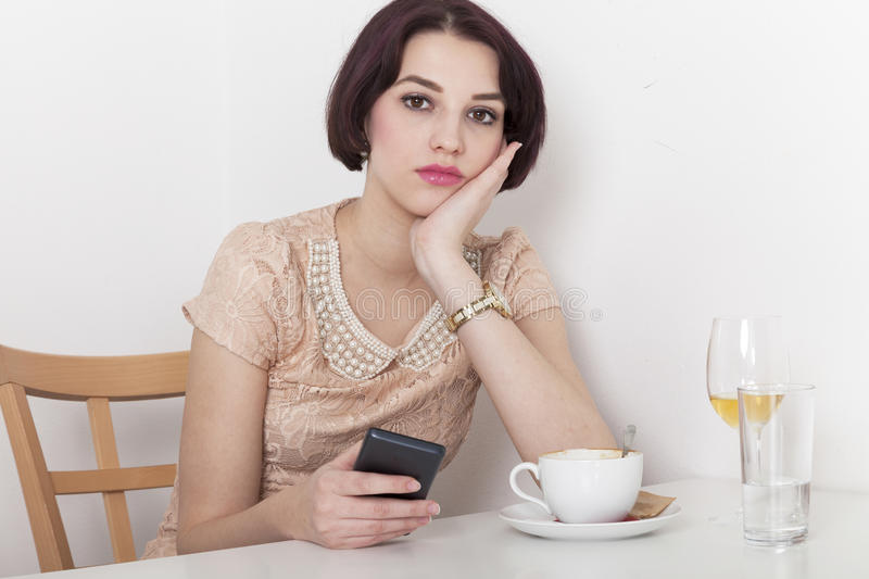 Woman looks disappointed to her mobile phone. Woman receives a message due to canceled date with her in a cafeteria stock image