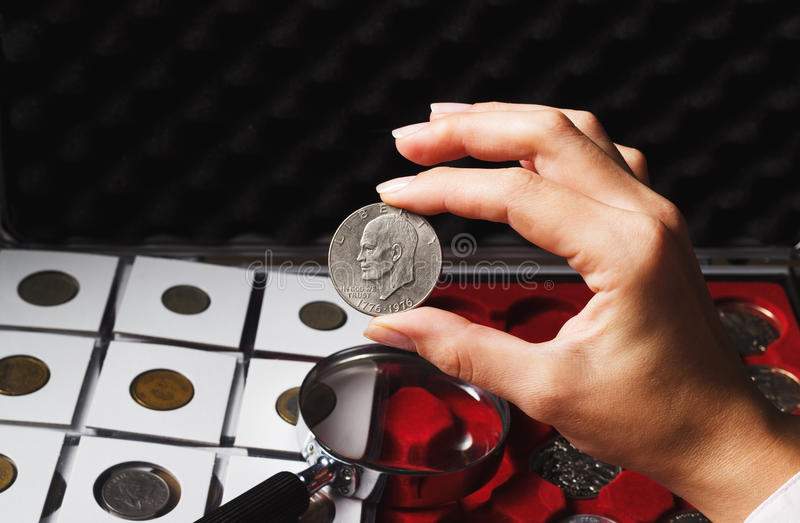 Woman looks at the Dollar coin. Woman looking at the collector`s Dollar coin, soft focus background royalty free stock photo