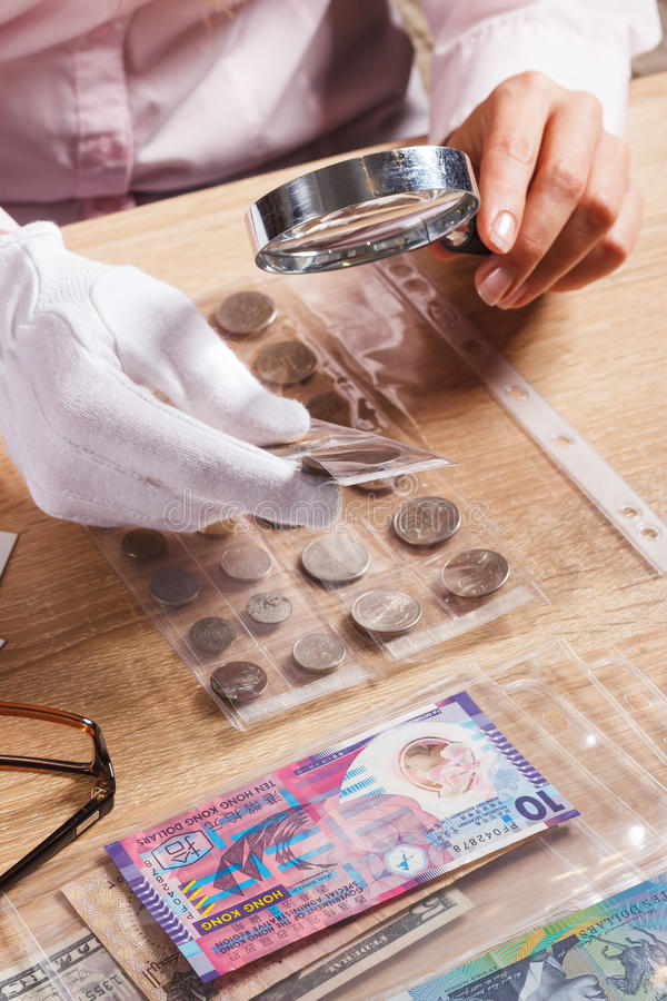 Woman looks at the Dollar coin through a magnifying glass. Woman looking at the Dollar coin through a magnifying glass, soft focus background royalty free stock photos